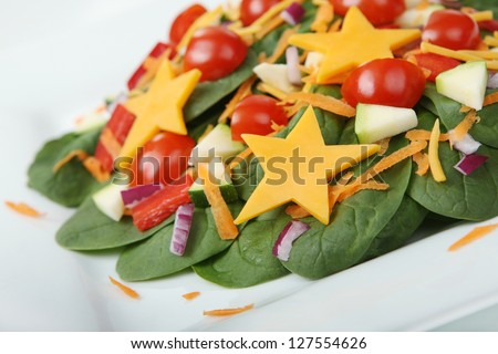 Healthy Spinach Salad with Kid-Friendly Cheese Stars on a White Plate (with focus on front edge of salad) - stock photo