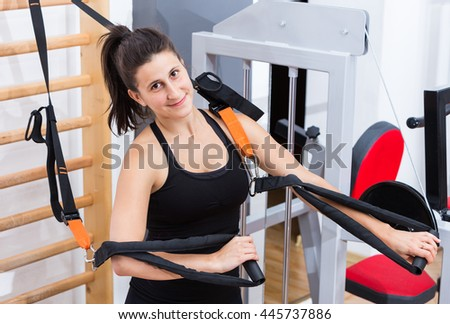 Healthy, sporty, attractive girl at the gym, in sportswear while making endurance chest body exercise, suspension training with her own weight.