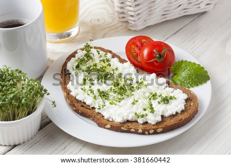 healthy spring summer low fat breakfast with orange juice,coffee,bread,cottage cheese, cress and tomatoes at white wooden table - stock photo