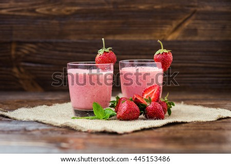 Healthy strawberry yogurt with mint leaves and fresh berries on a old wooden background. Yogurt with fresh strawberries. Strawberry milkshake in the glass - stock photo