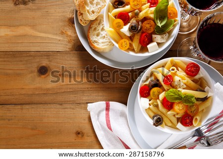 Healthy summer light pasta salad with fresh raw tomatoes, anchovies and capers. glasses of red wine. on wood