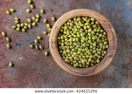 Healthy super food. Uncooked green mungo beans in olive wood bowl over old rusty iron background. Top view. Close up with copy space - stock photo