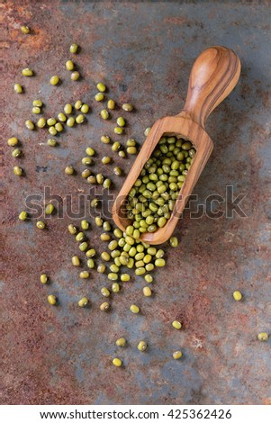 Healthy super food. Uncooked green mungo beans in olive wood scoop over old rusty iron background. Top view. - stock photo