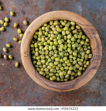 Healthy superfood. Uncooked green mungo beans in olive wood bowl over old rusty iron background. Top view. Close up. Square image - stock photo