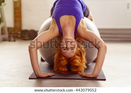 Healthy supple young redhead woman doing pilates in a gym bending backwards over a ball smiling happily at the camera with her hands on the ground - stock photo