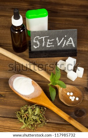 Healthy sweetener stevia in liquid tablet dried and powder forms, plus real sugar lumps - stock photo