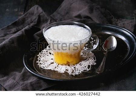 Healthy tapioca pearls pudding dessert with coconut milk and mango. Served in glass on vintage iron tray over old wooden table with black textile napkin. Dark rustic style. - stock photo