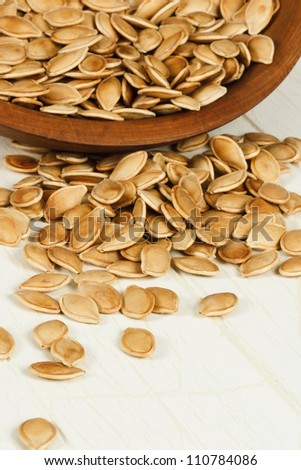 Healthy toasted pumpkin seeds spilling from a rustic wood bowl with focus on foreground seeds and copy space at bottom - stock photo