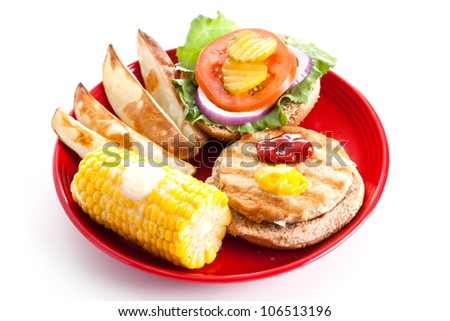 Healthy turkey burger on whole grain bun, with baked potato wedges and corn on the cob.  Isolated on white.
