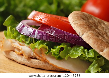 Healthy turkey sandwich on thin whole wheat deli roll with lettuce, onions and tomato on wooden cutting board with tomato and lettuce in background.  Macro with shallow dof. - stock photo
