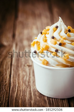 Healthy twirl of low fat frozen yoghurt parfait topped with sprinkles served in a white plastic takeaway tub on an old rustic wooden counter top with copyspace - stock photo