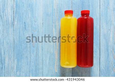 Healthy vegan drinks, fruit smoothie flat lay, top view at blue rustic wood background. Berry and orange healthy, dieting energetic fruit drinks in bottles with copyspace. Smoothie in bottles. - stock photo