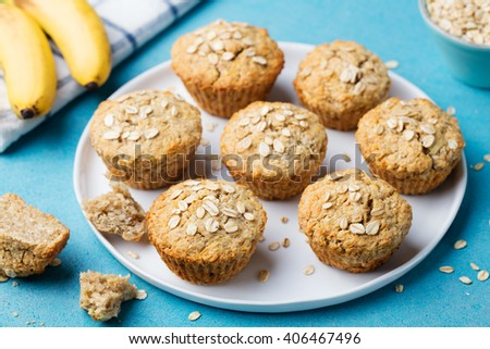 Healthy vegan oat muffins, apple and banana cakes on a white plate Blue stone background - stock photo