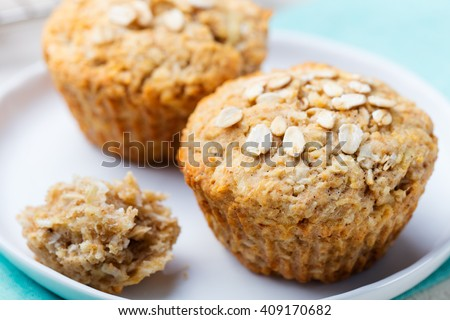 Healthy vegan oat muffins, apple and banana cakes with sour cream on a white plate Blue stone background - stock photo