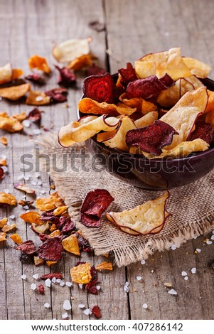 Healthy vegetable beetroot, sweet potato and white sweet potato chips on a bowl on a rustic background. Selective focus - stock photo