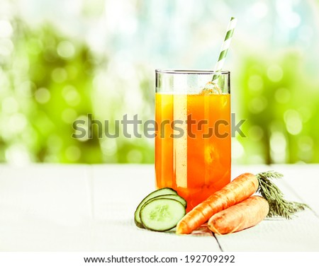 Healthy vegetable juice blend of carrot and cucumber rich in vitamins and carotene on a white wooden picnic table for a delicious summer treat - stock photo
