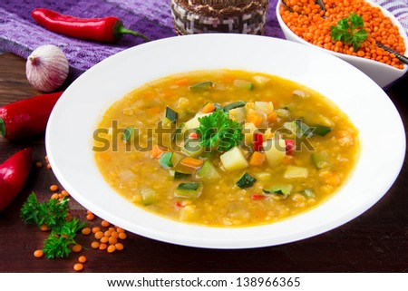 Healthy vegetable soup with red lentils, chili pepper and zucchini in a white ceramic plate