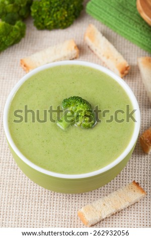Healthy vegetarian broccoli green cream soup with croutons in bowl on wooden background