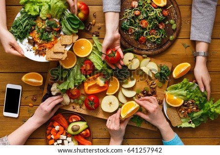 Healthy vegetarian dinner table. Women at home together, eating fruits and vegetables, top view, flat lay, crop
