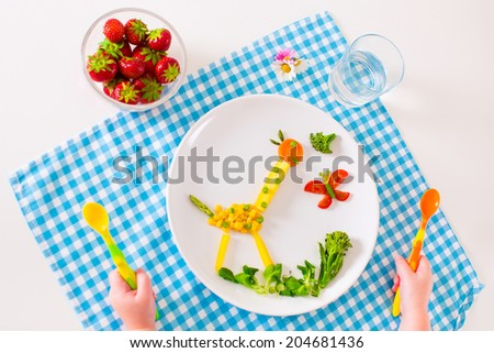 Healthy vegetarian lunch for little kids, vegetables and fruit served as animals, corn, broccoli, carrots and fresh strawberry helping to learn eating right and clean, child's hands holding spoon - stock photo