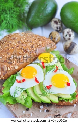 Healthy vegetarian sandwich with avocado, eggs, lettuce salad and hot pepper - stock photo