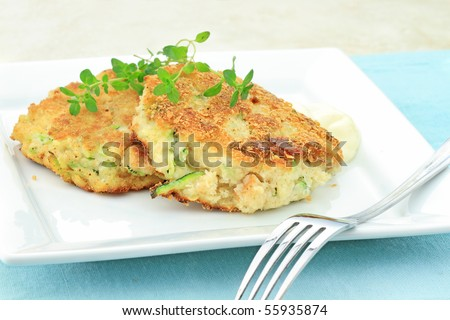 "Healthy vegetarian Zucchini ""Crab Cakes"" served with horseradish sauce and a sprig of thyme."