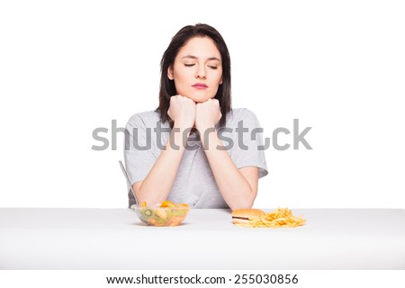 healthy versus junk food concept with a natural woman heaving in front fruits meal and fries with hamburger, isolated on white - stock photo