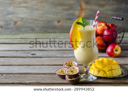 Healthy vitamin tropical mango and passion fruit smoothie with yogurt and peaches, milkshake, copy space background - stock photo