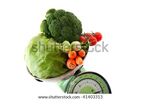 Healthy weight with fresh vegetables at a scale
