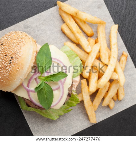 Healthy wheat sandwich burger with beef steak, cheese, tomato, lettuce, onion, basil, fried potato and ketchup  served for eating - stock photo