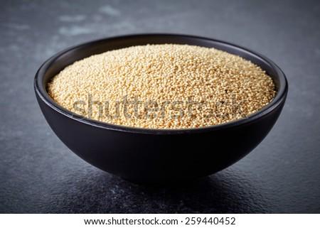 healthy white amaranth seeds in black bowl on dark background - stock photo