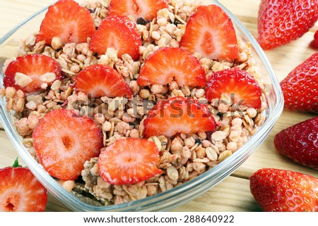 Healthy whole grain muesli and bran breakfast with strawberries - stock photo