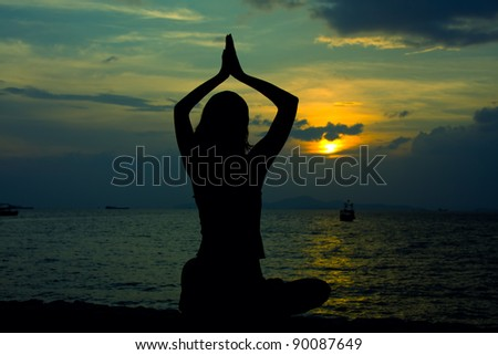 Healthy woman doing yoga outdoor, sunset over sea