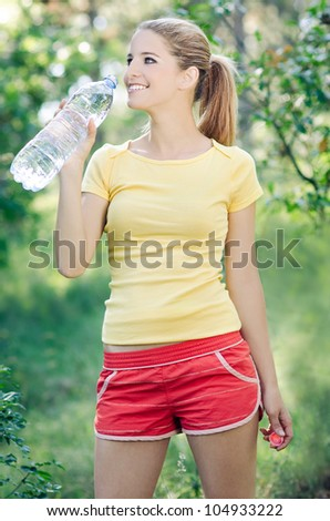 Healthy woman drinks water, doing sport outdoor, fitness, diet & body care concept - stock photo