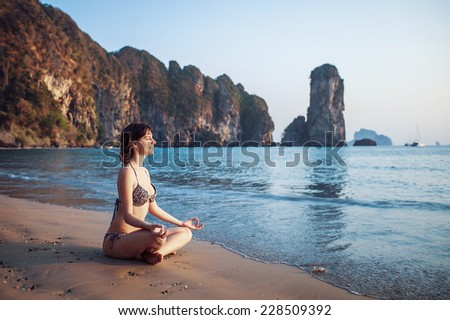 healthy woman practicing yoga on the beach at sunset - stock photo