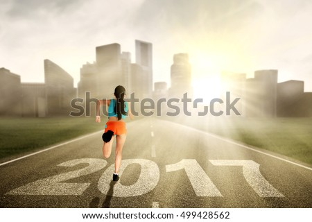 Healthy woman running on the road while wearing sportswear with numbers 2017