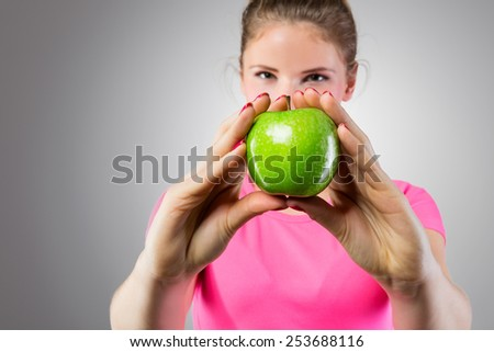 Healthy woman showing green apple - stock photo