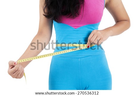 Healthy woman with sportswear use a measurement tape to measure her waist after workout - stock photo