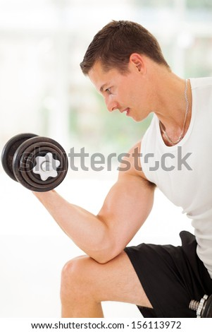 healthy young athlete lifting weights in the gym - stock photo