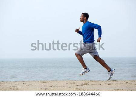 Healthy young athletic man running at the beach - stock photo