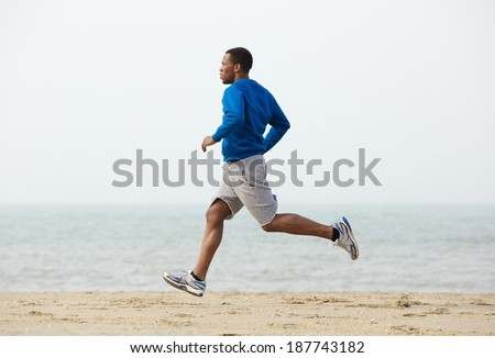 Healthy young black man jogging at the beach - stock photo