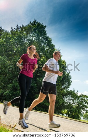 Healthy young couple jogging in a park - stock photo