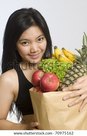 Healthy young girl holding a bag of groceries - stock photo