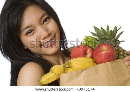 Healthy young girl holding a bag of groceries