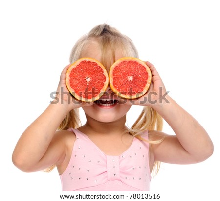 healthy young girl uses grapefruit as eyes and has fun in studio