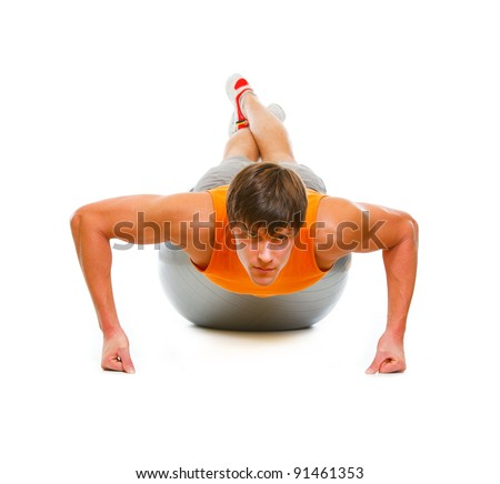 Healthy young man  making push up exercise on fitness ball isolated on white