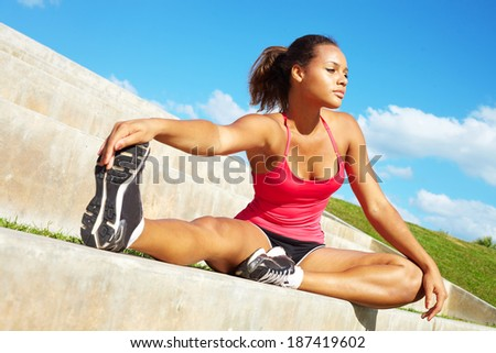 healthy young pretty mixed race woman stretching her leg during exercise in grass right before a work out. Horizontal shot. - stock photo