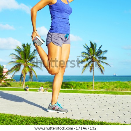 healthy young pretty mixed race woman stretching her leg during exercise on running trail near ocean right before a work out.  - stock photo