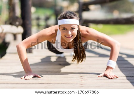 healthy young woman doing pushups outdoors - stock photo