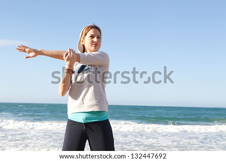 Healthy young woman exercising and stretching while standing on a beach with an intense blue sky and the sea in the background.